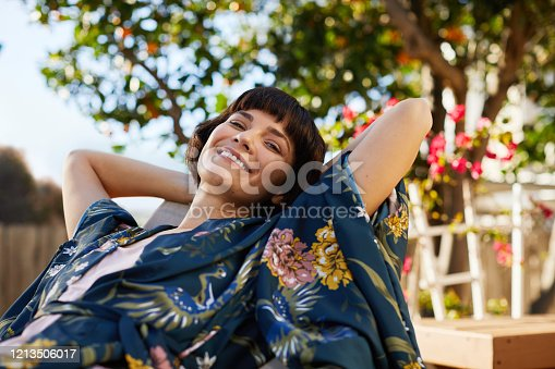 Portrait of a smiling young woman in a robe lying on a deck chair outside on a sunny afternoon