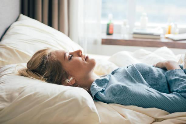 mulher sorridente deitada na cama e ouvindo música através de seus fones de ouvido sem fio - meditation - fotografias e filmes do acervo