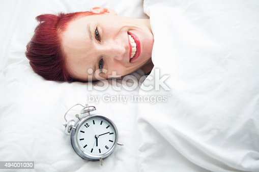 509031214istockphoto smiling woman lying in bed with alarm clock on pillow 494001030