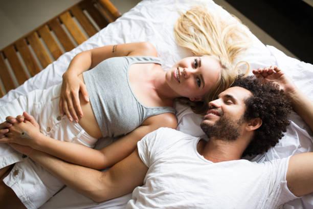 Smiling woman lying near sleeping boyfriend stock photo
