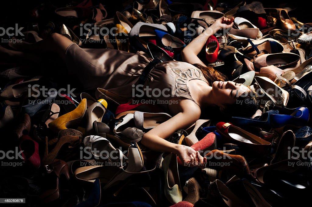 Smiling woman lying on high heels stock photo