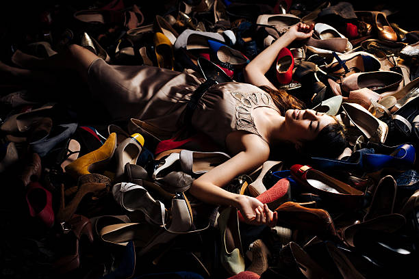Smiling woman lying on high heels stock photo