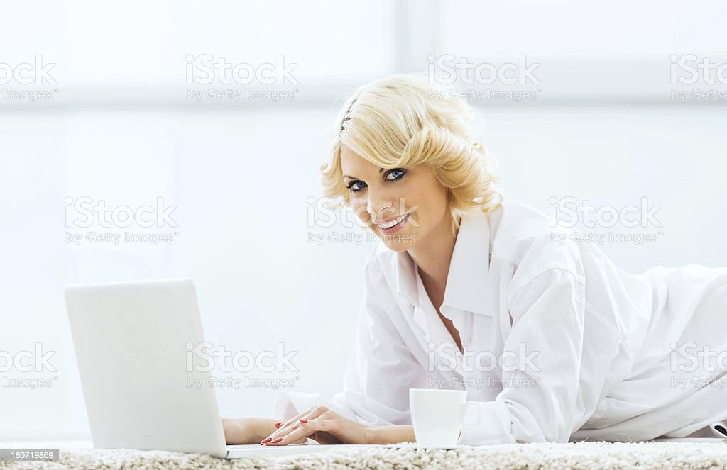 Smiling woman lying on the carpet. royalty-free stock photo