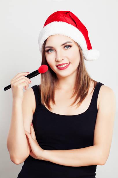 Smiling Woman Makeup Artist wearing Christmas Santa Hat stock photo