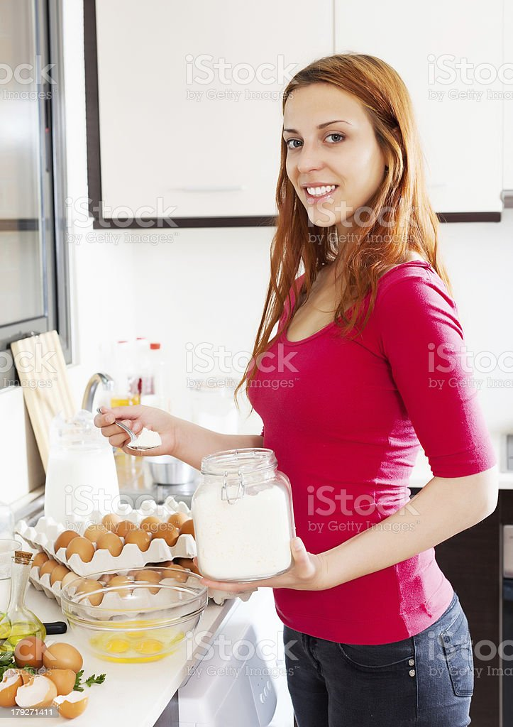 Smiling woman making dough with flour royalty-free stock photo