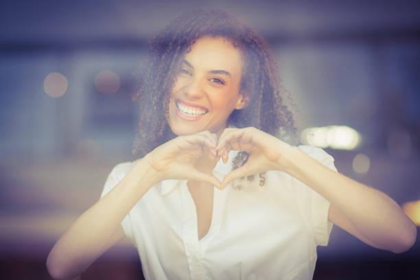 mulher sorridente fazendo formato de coração - dia do cliente - fotografias e filmes do acervo
