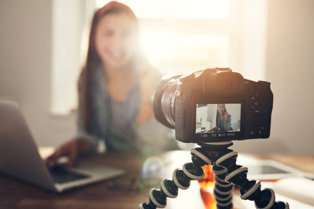smiling woman making vlog and looking at camera - vlogger stock photos and pictures