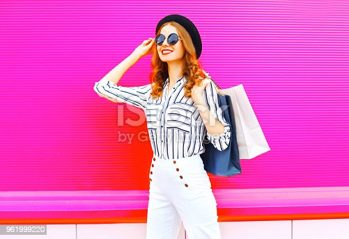 istock Smiling woman model with shopping bags wearing a black hat white pants over colorful pink background 961999220
