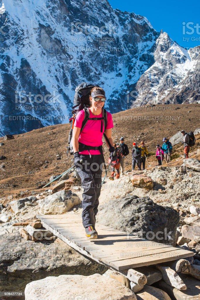 Smiling woman mountaineer hiking on Himalaya mountain trail Khumbu Nepal stock photo