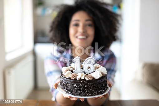 Smiling african woman holding birthday cake, looking at camera.