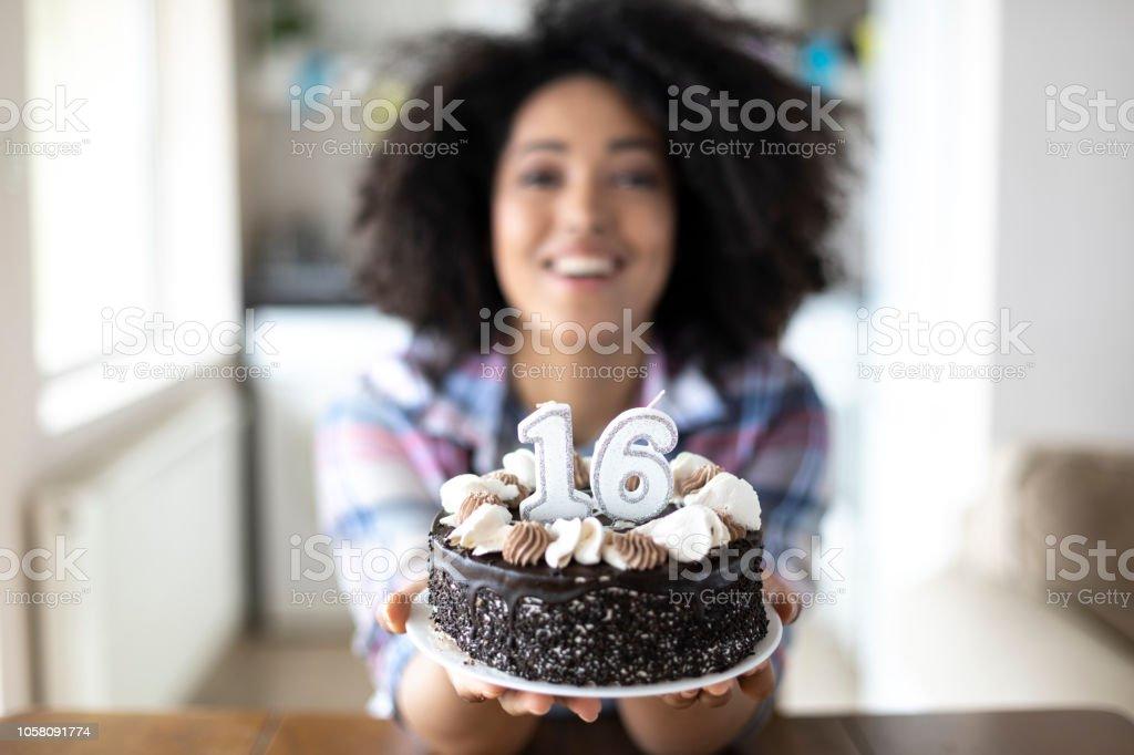 Mulher sorridente, oferecendo um bolo de aniversário - foto de acervo