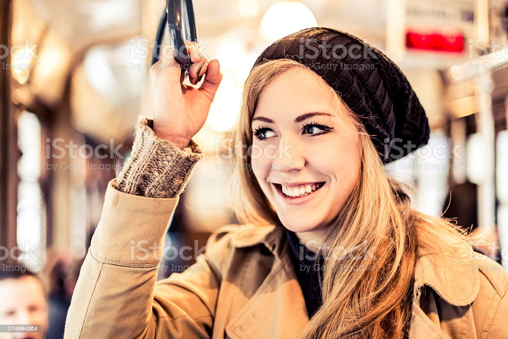 Smiling woman on a tram holding the overhead handle royalty-free stock photo