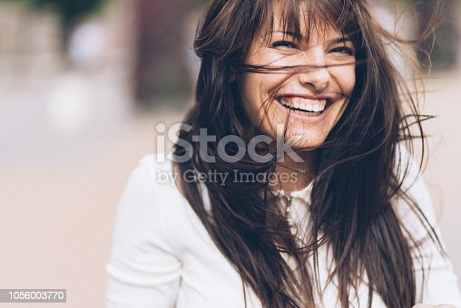 Beautiful charming woman with messy hair outdoor in windy day