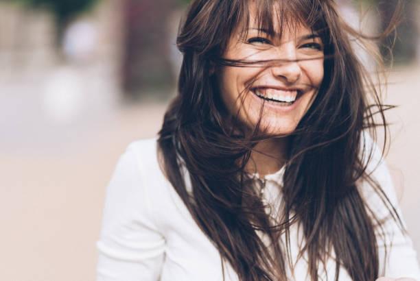 femme souriante sur une journée venteuse - sourire à pleines dents photos et images de collection