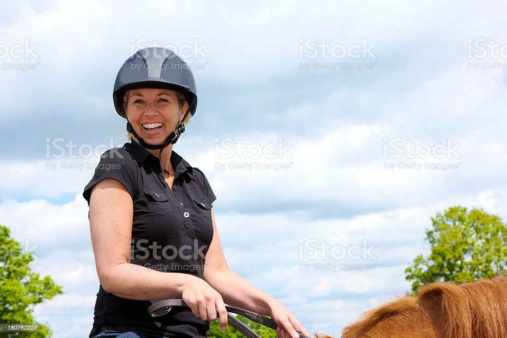 Smiling woman on horseback outdoors learning to ride a horse stock photo