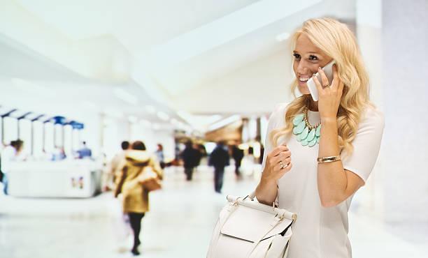 lächelnde frau auf handy in der shopping mall - canda armband stock-fotos und bilder