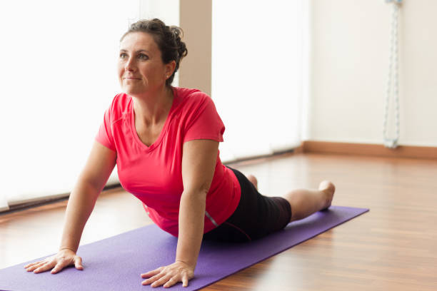 Smiling woman on purple mat doing upward facing dog yoga pose Pretty female yogi practicing urdhva mukha svanasana in studio. Exercise, pilates, workout, sport outfit, healthy lifestyle concepts upward facing dog position stock pictures, royalty-free photos & images