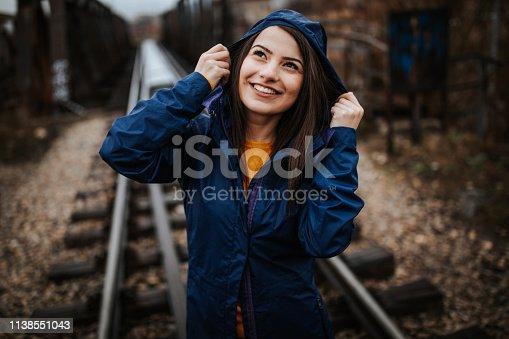 Young woman on railway bridge at rainy day