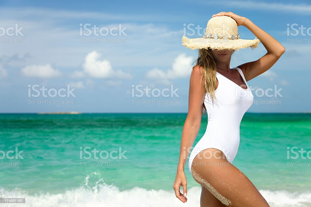 smiling woman on shoreline of tropical beach stock photo