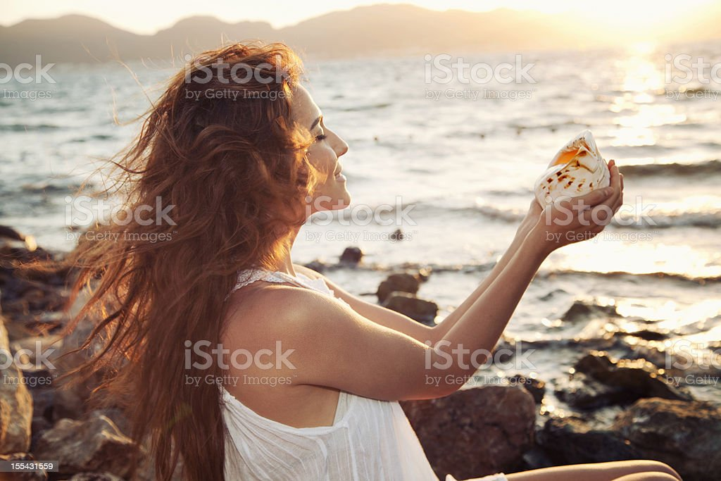 Smiling woman on the beach with seashell stock photo