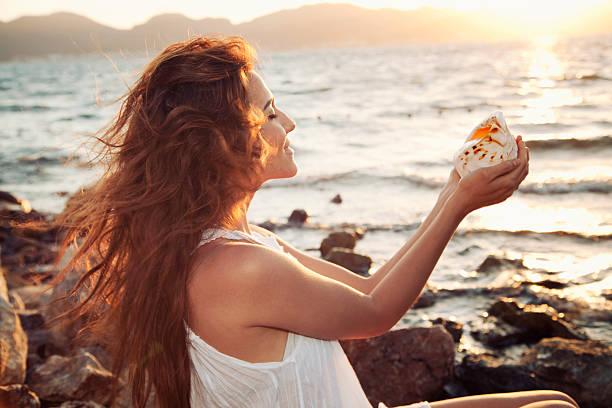 lächelnde frau am strand mit seashell - haare ohne lockenstab wellen stock-fotos und bilder