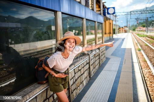 Happy smiling Latin woman on the train station waiting for the train. She is pointing