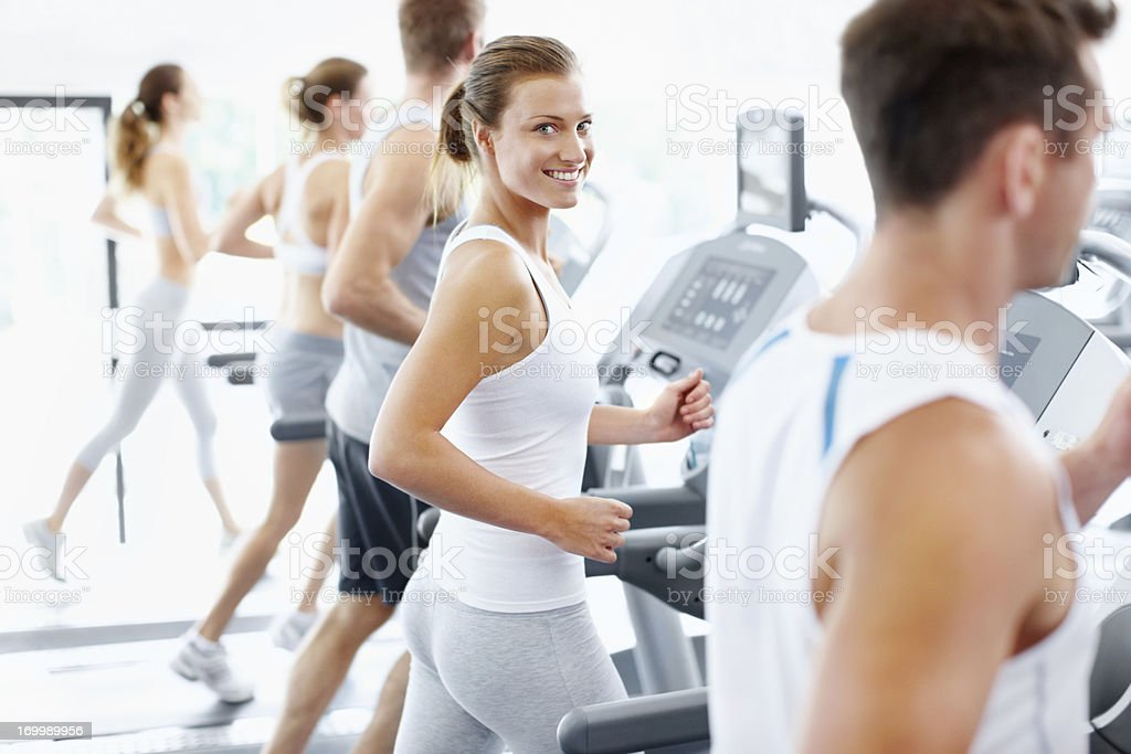 Smiling woman on treadmill alongside other members royalty-free stock photo
