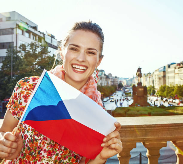 smiling woman on Vaclavske namesti in Prague showing flag The spirit of old Europe in Prague. Portrait of smiling modern woman on Vaclavske namesti in Prague, Czech Republic showing flag wenceslas square stock pictures, royalty-free photos & images