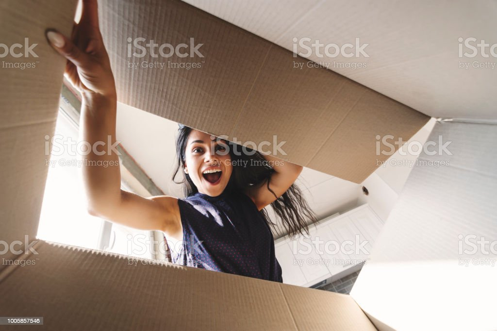 Smiling woman opening a carton box stock photo