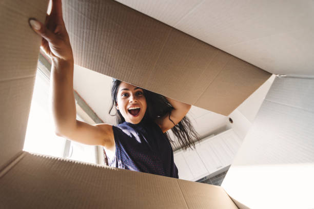smiling woman opening a carton box - astonishment stock photos and pictures