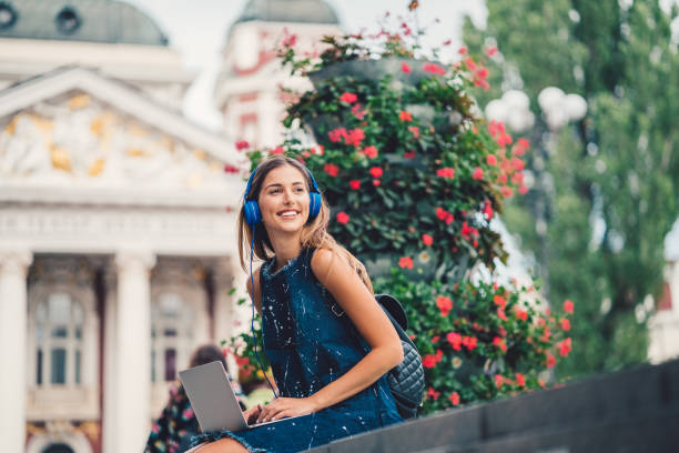 Smiling woman outside using laptop and listening to podcasts picture id850887488?b=1&k=6&m=850887488&s=612x612&w=0&h=fpslhotm0rec8p2dyspqkrcm0tydbk 8knpdmp0w99o=
