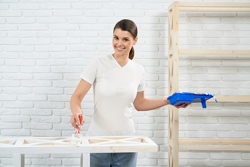 Smiling woman painting with brush wooden shelves