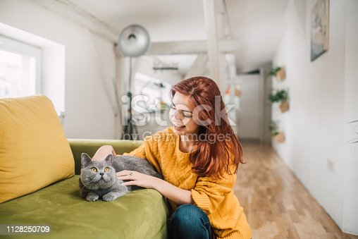 istock Smiling woman pampering a cat 1128250709