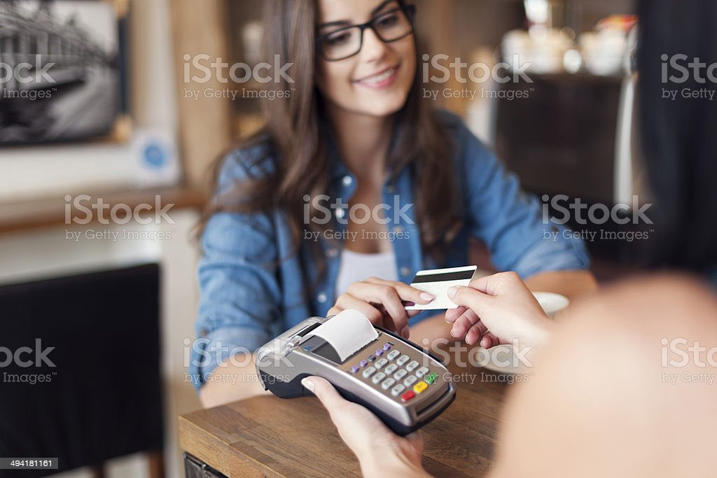 Smiling woman paying for coffee by credit card stock photo