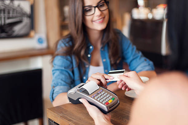 Smiling woman paying for coffee by credit card Smiling woman paying for coffee by credit card  credit card purchase stock pictures, royalty-free photos & images
