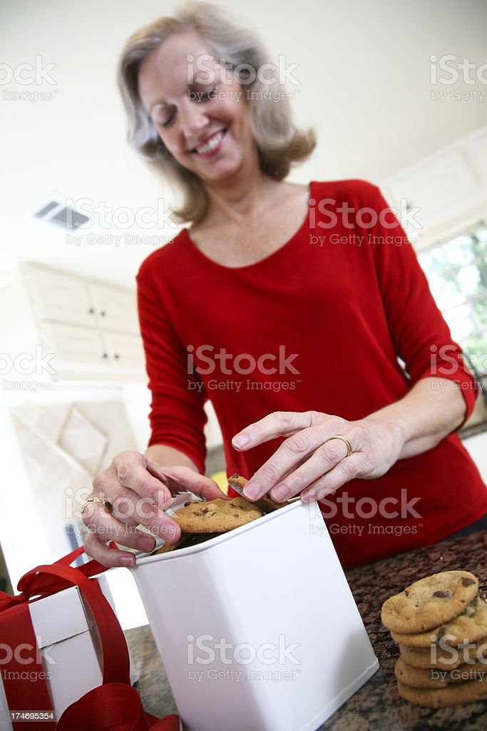 Smiling Woman Placing Chocolate Chip Cookies in Gift Box royalty-free stock photo