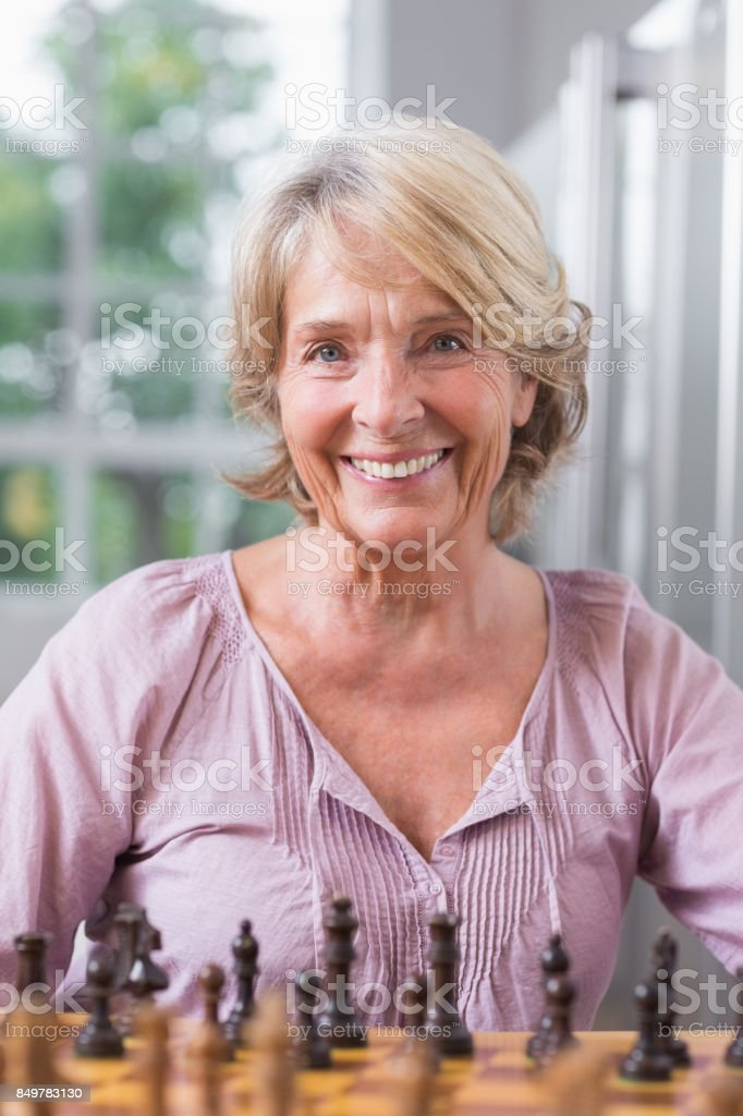 Smiling woman playing chess stock photo