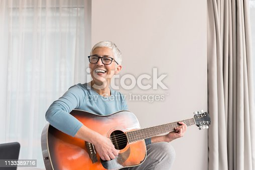 Cheerful charming beautiful mature woman enjoy playing guitar, Musical hobbies concept