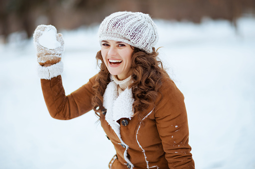 smiling modern 40 years old woman with mittens in a knitted hat and sheepskin coat playing snowball outside in the city park in winter.