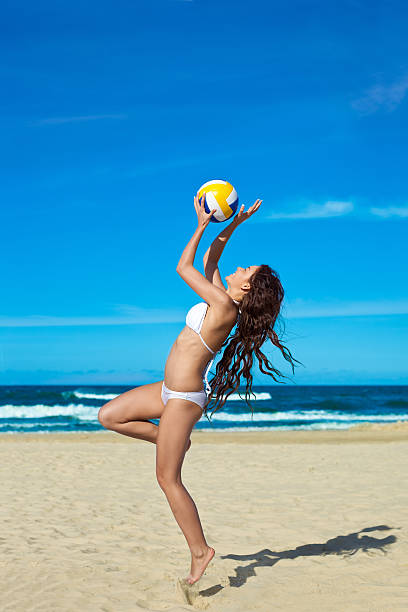 Smiling woman playing volleyball stock photo
