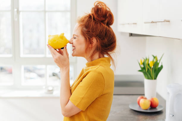 Smiling woman playing with piggy bank stock photo