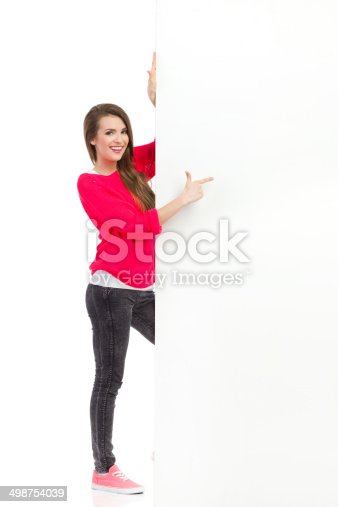 istock Smiling woman pointing at big white placard 498754039