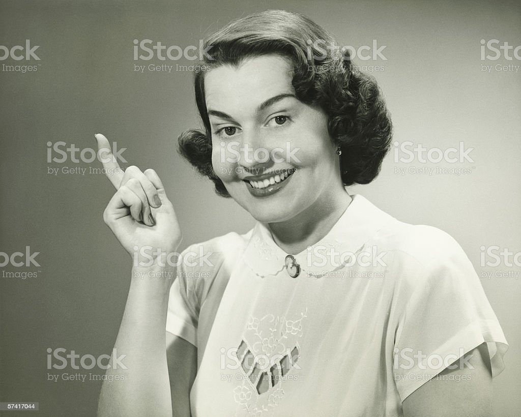 Smiling woman pointing finger in studio, (B&W), (Close-up), (Portrait) stock photo