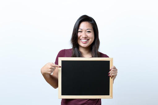 istock Smiling woman pointing to a blank blackboard 657342426