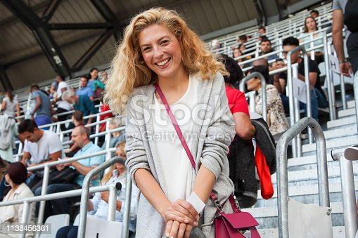 Young woman coming to a football match. Smiling portrait.