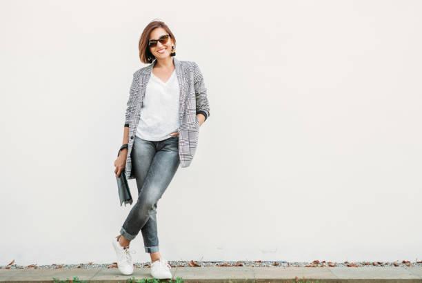 lächelnde frau posiert in casual city-outfit in den farben schwarz und grau - handtasche jeans stock-fotos und bilder
