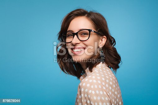 876629044istockphoto Smiling woman posing in glasses 876629044