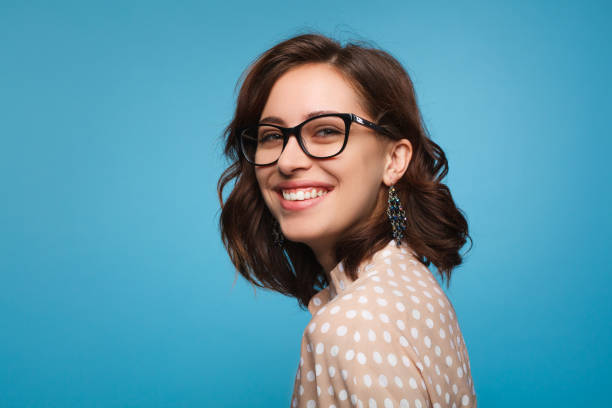 Smiling woman posing in glasses Elegant cheerful brunette in eyeglasses smiling at camera on blue background. studio stock pictures, royalty-free photos & images