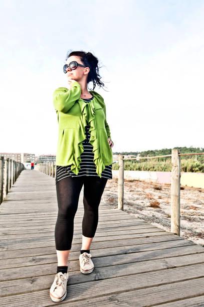 lächelnde frau posiert auf einem pier/holzbrücke - damen leggings übergrößen stock-fotos und bilder