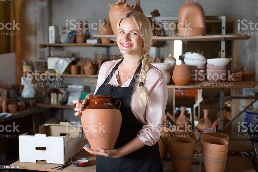 Smiling woman potter carrying ceramic vessels royalty-free stock photo